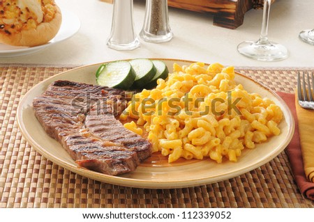 A grilled steak with macaroni and cheese