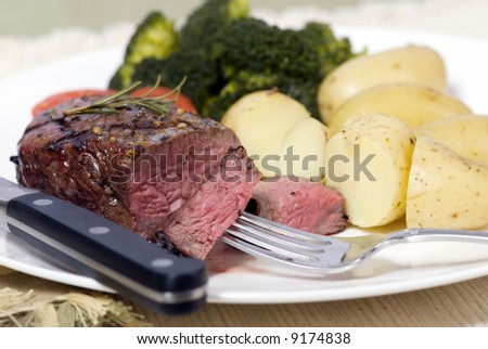 A grilled top sirloin steak .. medium with broccoli and fresh baby potatoes - stock photo