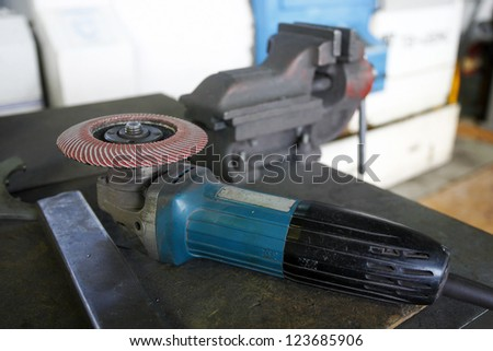 A grinder and other working tools on a factory table - stock photo