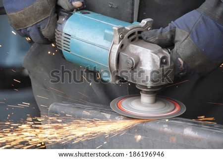 A grinder is used to smooth a welding seam on a metal bar/Grinder/A grinder is used to smooth a welding seam on a metal bar