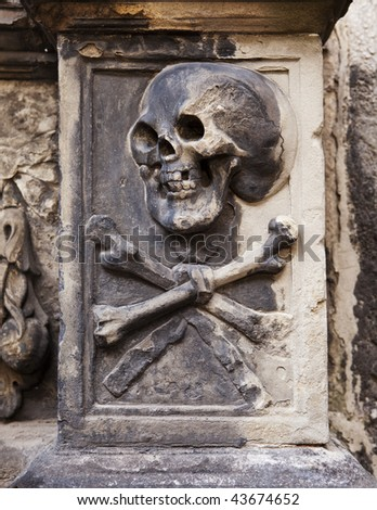 A grisly image of death grimacing with a skull and crossbones on a headstone in Holyrood Abbey in Edinburgh, Scotland. - stock photo