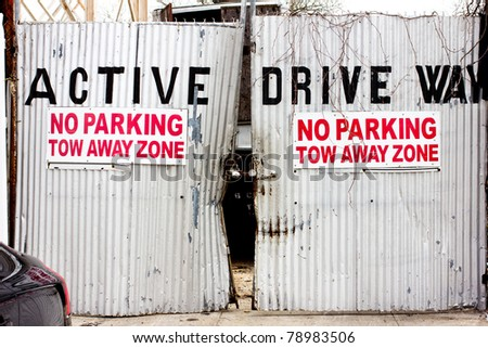 A gritty urban sign warns of 'no parking' in tow away zone on locked driveway gates