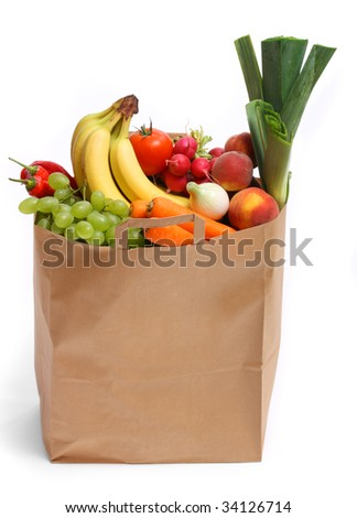 A grocery bag full of healthy fruits and vegetables - stock photo