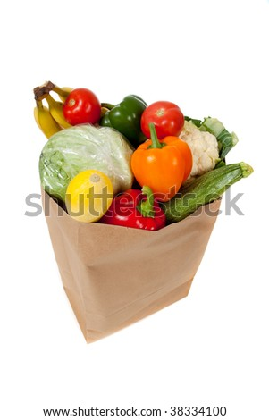 A grocery sack full of vegetables on a white background - stock photo