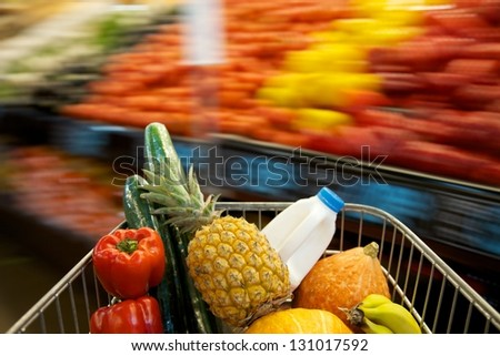 A grocery shopping cart filled with different products including milk, banana's, cucumbers and pineapple with a motion blurred background - stock photo