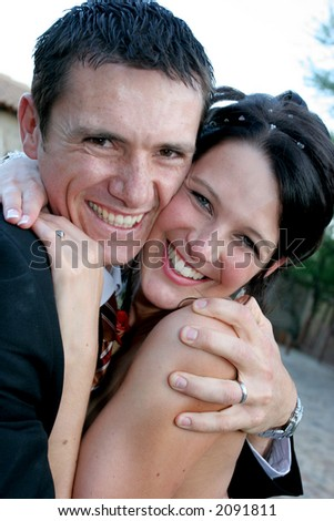 A groom and bride squeezing each other tight - stock photo