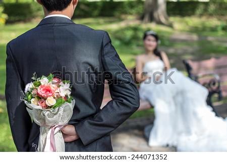 A groom hiding a flower bouquet faced toward his bride - stock photo