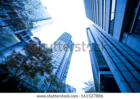 A ground view looking towards the sky with buildings and trees. - stock photo