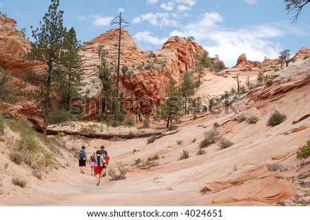 A group hikes in the red rock area of the southwest USA. - stock photo
