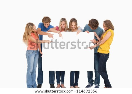 A group holding a blank sheet and pointing to it while smiling - stock photo