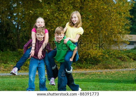 A group of active, healthy children giving each other piggy back rides outside. - stock photo