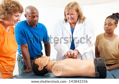 A group of adult education students watch a doctor or nurse demonstrating CPR chest compressioon on a dummy.