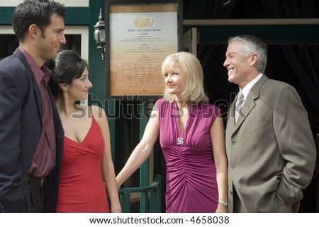 A group of adults outside a restaurant - stock photo