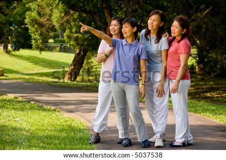 A group of Asian women standing together in the park looking at something of interest - stock photo