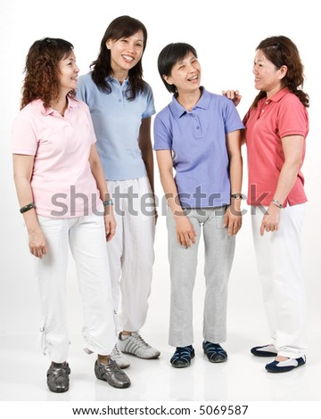 A group of Asian women standing together in the studio talking - stock photo