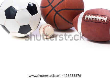 A group of assorted sports balls on white background with copy space.  Including a soccer ball a baseball a basketball and an American football. - stock photo