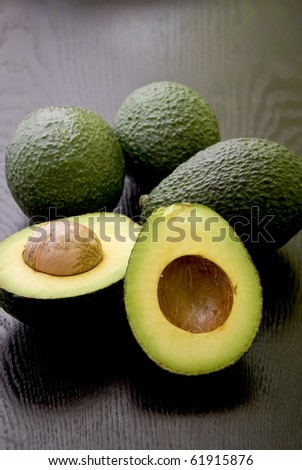 A group of avocado on a dark table. - stock photo