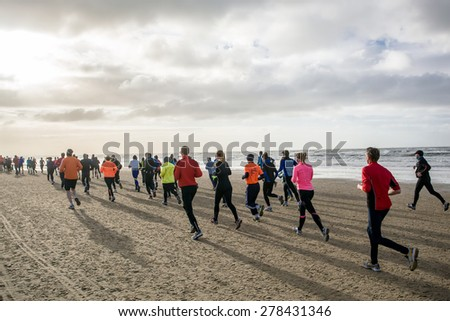 A group of back lit people in colorful outfits are running during a marathon that goes partly over a beach - stock photo