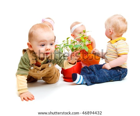 A group of beautiful babies sitting, one is crawling - stock photo