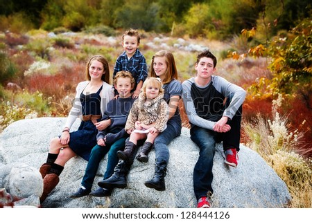 A group of beautiful children sitting on a rock with a Fall background - stock photo