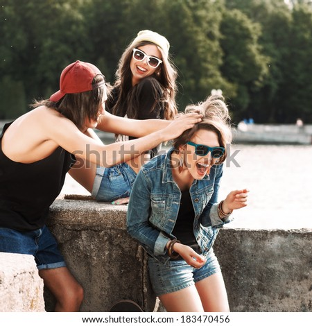 a group of beautiful young people with basketball and skateboard have fun by river handrail - stock photo