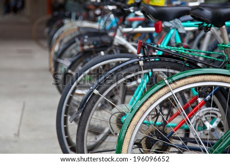 A group of bicycles parked on a street. - stock photo