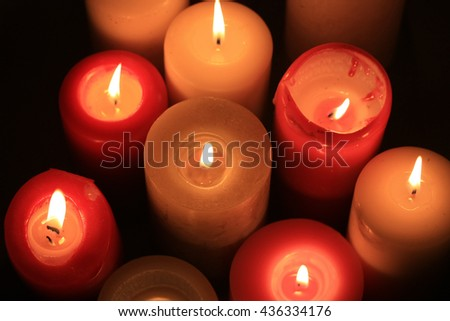 A group of burning candles in different colors - stock photo