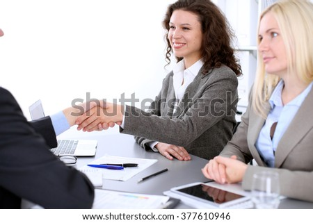 A group of business people at a meeting on the background of office. Business handshake. Focus on a beautiful blonde