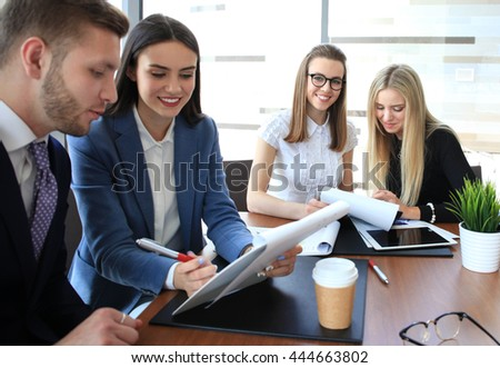 A group of business people at a meeting on the background of office. Focus on a beautiful brunette - stock photo