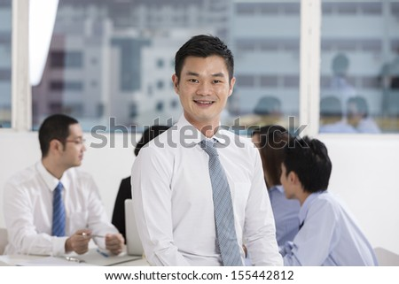 A group of business people lead by a happy Chinese Business man.