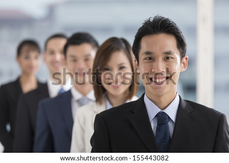 A group of business people lead by a happy Chinese Business man. - stock photo