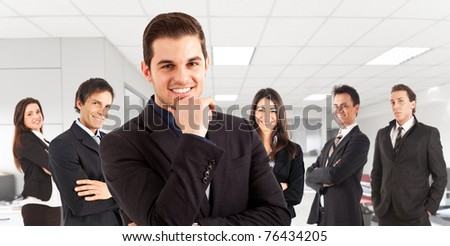 A group of businessmen and businesswomen in an office environment, their leader is on the front - stock photo