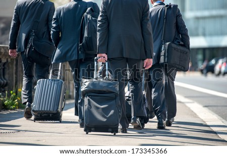 A group of businessmen pulling suitcases with luggage - stock photo