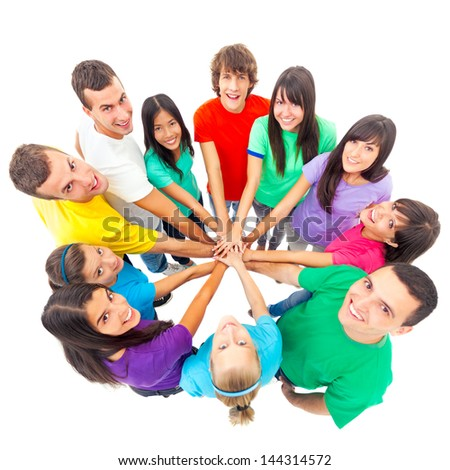 A group of cheerful people showing their unity by putting their hands one on top of the other. - stock photo
