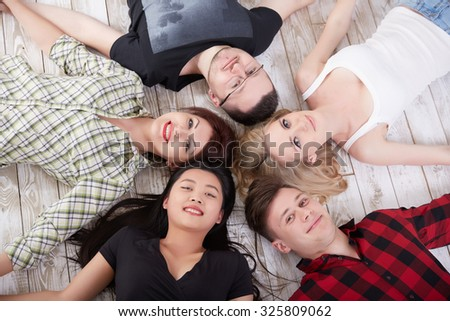 a group of cheerful students lying on the floor all around