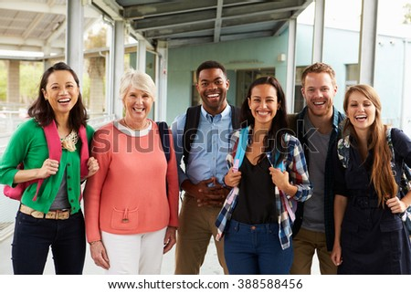 A group of cheerful teachers hanging out in school corridor - stock photo