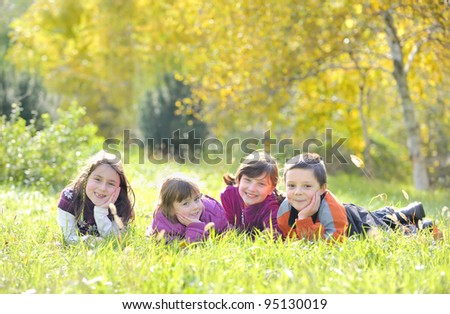 A group of children laying down in the grass - stock photo