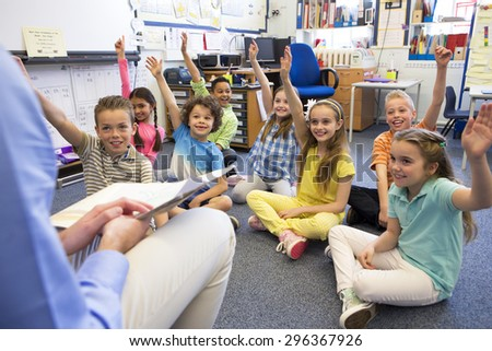 A group of children sit on the floor cross legged, listening to the teacher. They all have their hands raised in the air to answer a question. - stock photo