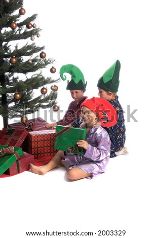 A group of children sitting under the Christmas Tree and excitedly examining the presents