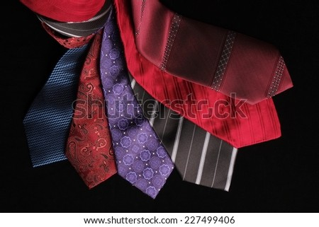 A group of classic and modern silk ties set in spiral arrangement, view from above. Blue, red , purple, bordeaux and black colors - stock photo
