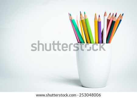A group of color pencils in a white cup on an isolated background - stock photo