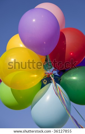 A group of colorful balloons with blue sky background