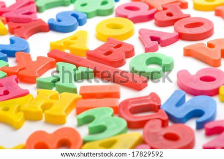 "A group of colorful plastic alphabet letter magnets on a white background, focus is on the ""B"" in ABC."