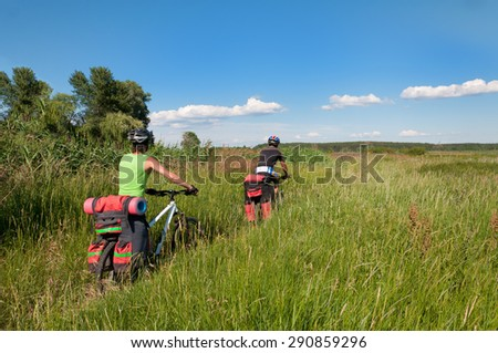 A group of cyclists on a mountain bike rides through the tall grass. Ukraine.