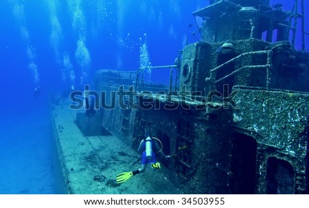 A group of divers are swimming around the deck of the Tibbetts, a Russian frigate that was sunk in the waters off Cayman Brac. - stock photo