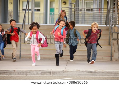 A group of elementary school kids rushing out of school - stock photo