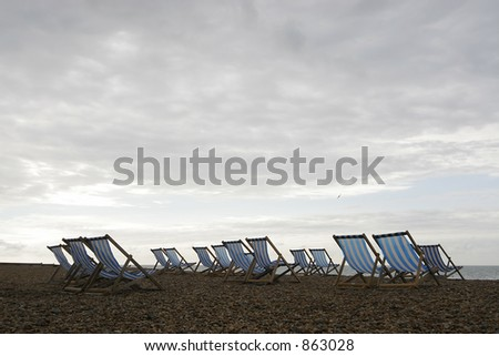 A group of empty deckchairs on a cloud covered beach in the early morning - stock photo