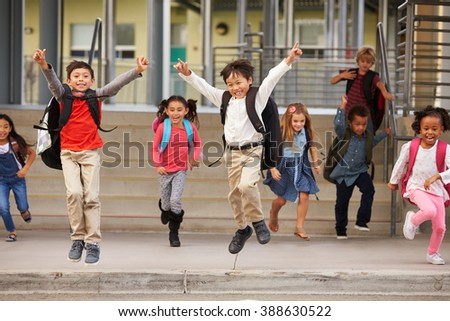 A group of energetic elementary school kids leaving school - stock photo