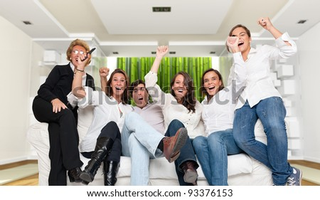A group of family members sitting in a modern interior  cheering - stock photo