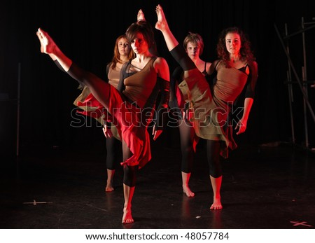 A group of female freestyle hip-hop dancers in a dancing training session. Lit with spotlights. Movement on edges of dancers, kicking high.